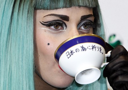 "Lady Gaga holds a teacup with the words ""Pray for Japan"" written on it as she attends a news conference in Tokyo"