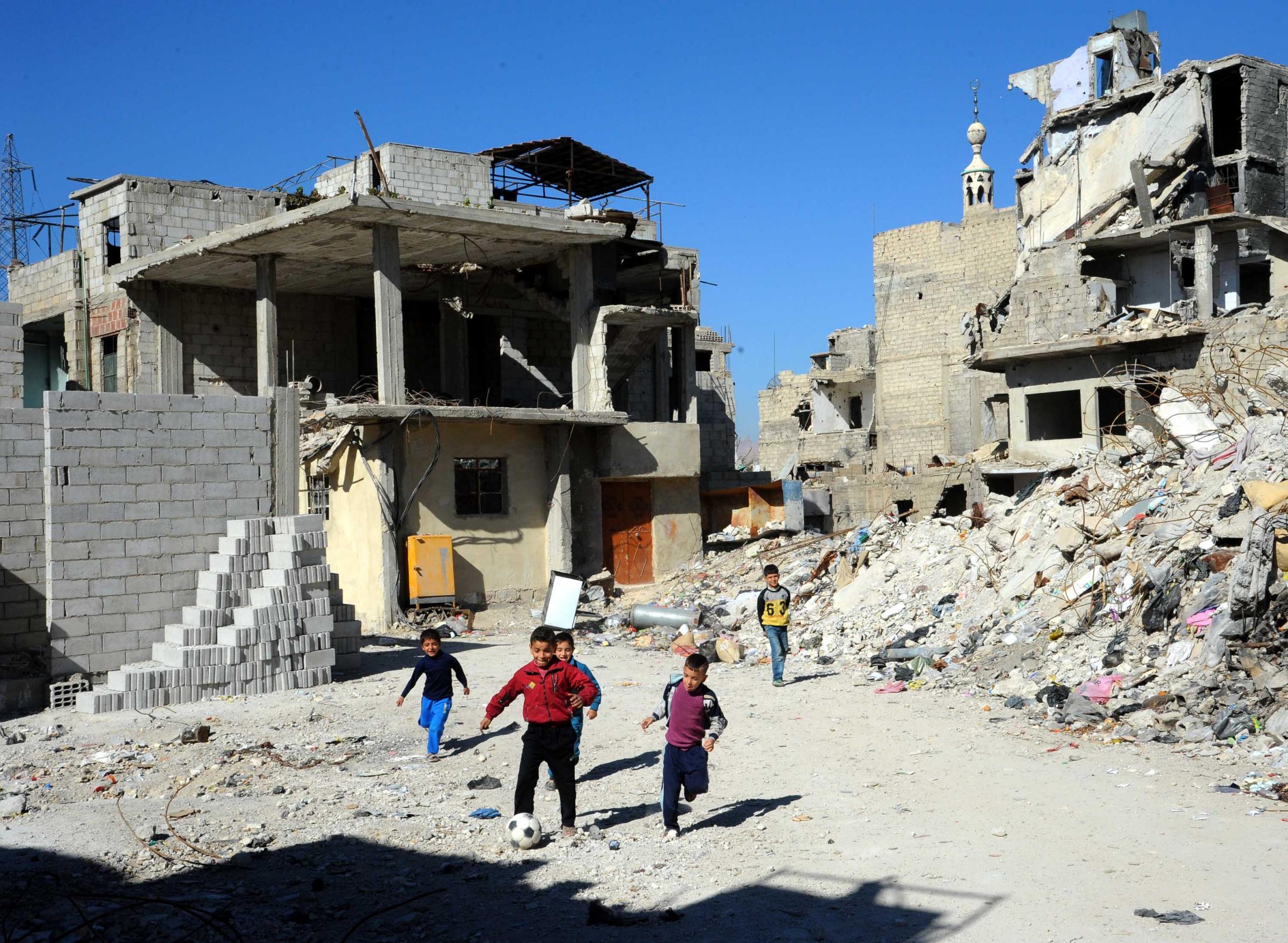 Siria, bambini giocano nelle zone colpite di Damasco