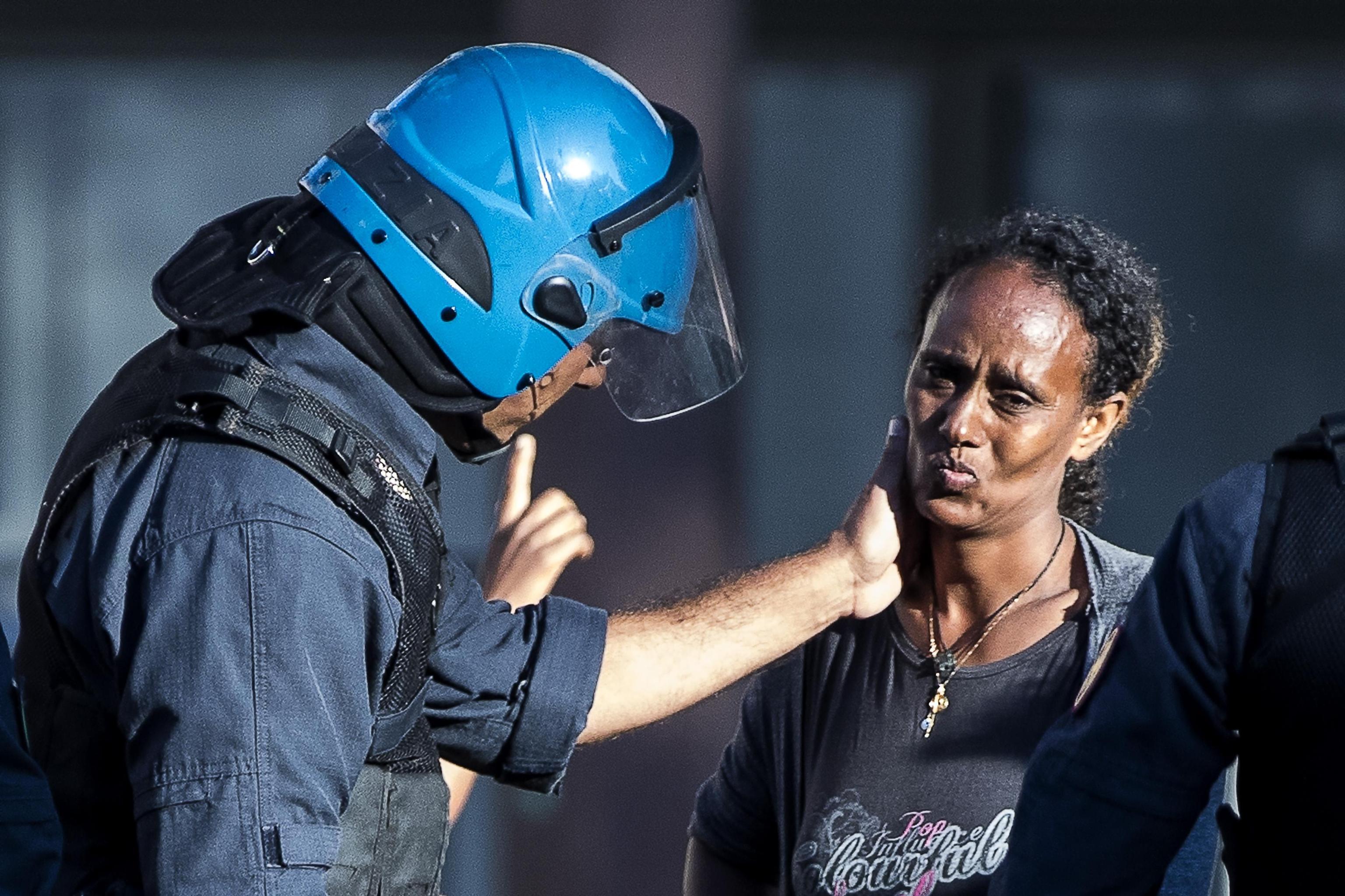 Sgomberi di Roma,  la carezza del poliziotto alla migrante eritrea: la foto-simbolo del dramma