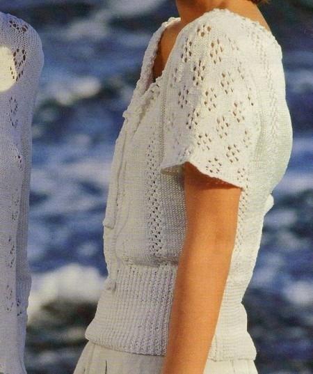 Lavori a maglia per creare una t-shirt bianca rifinita all'uncinetto