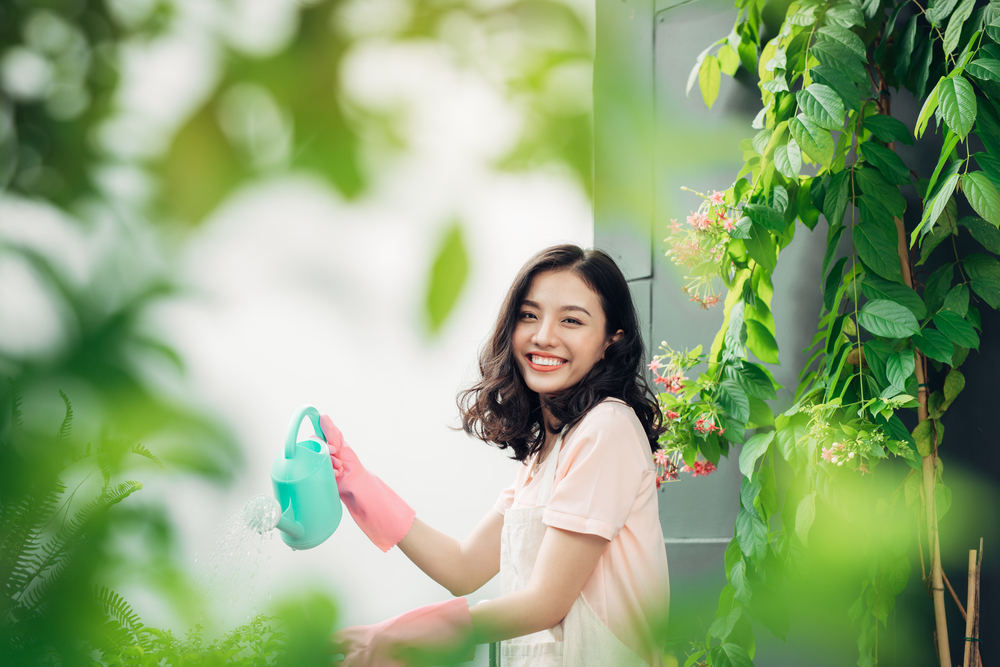 ragazza che innaffia le piante da frutto sul suo balcone