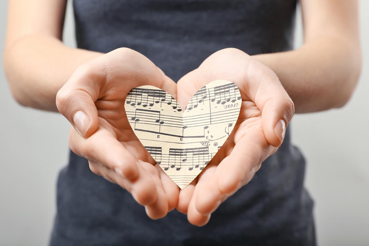 Ragazza con un cuore fatto di carta di spartito