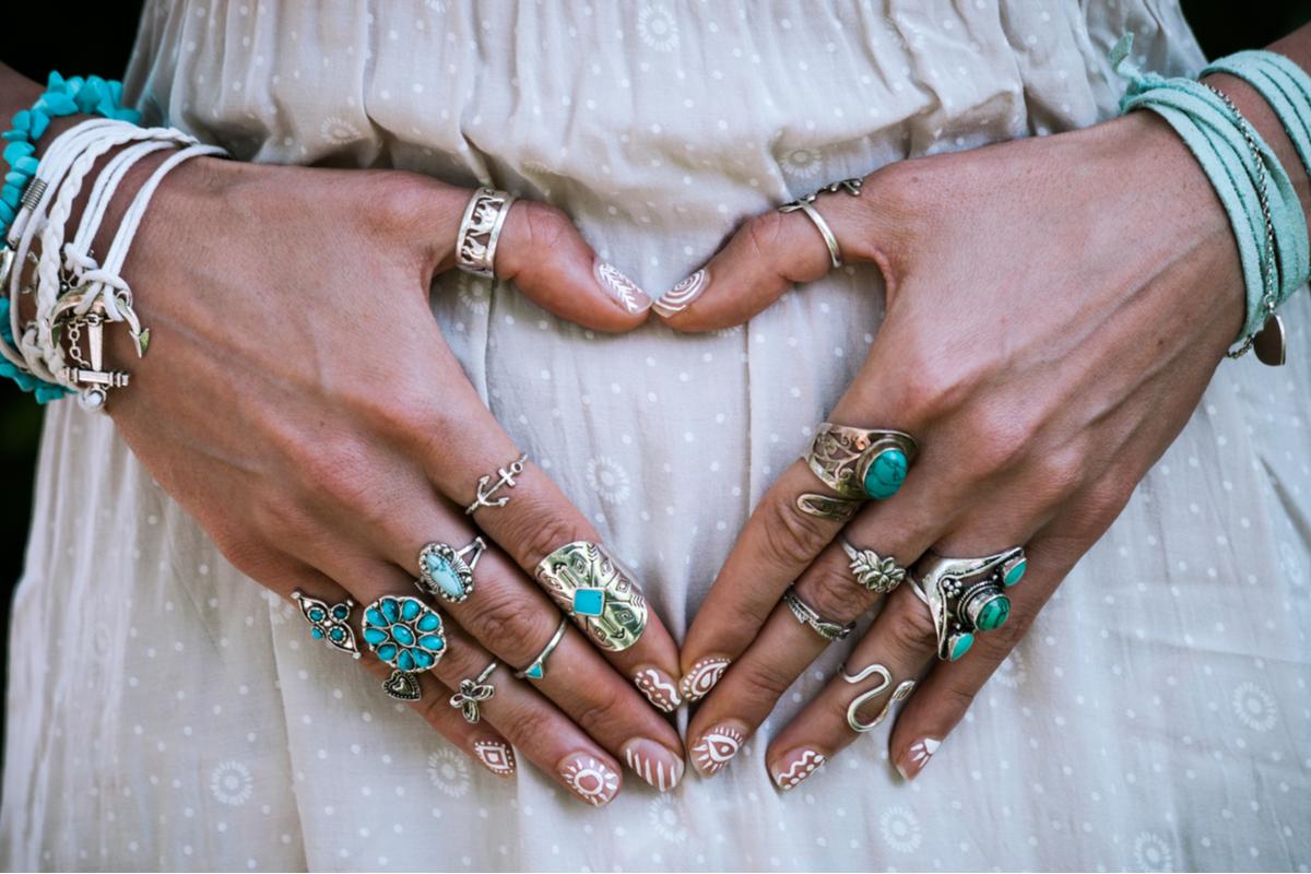 Mani con tanti anelli turchesi