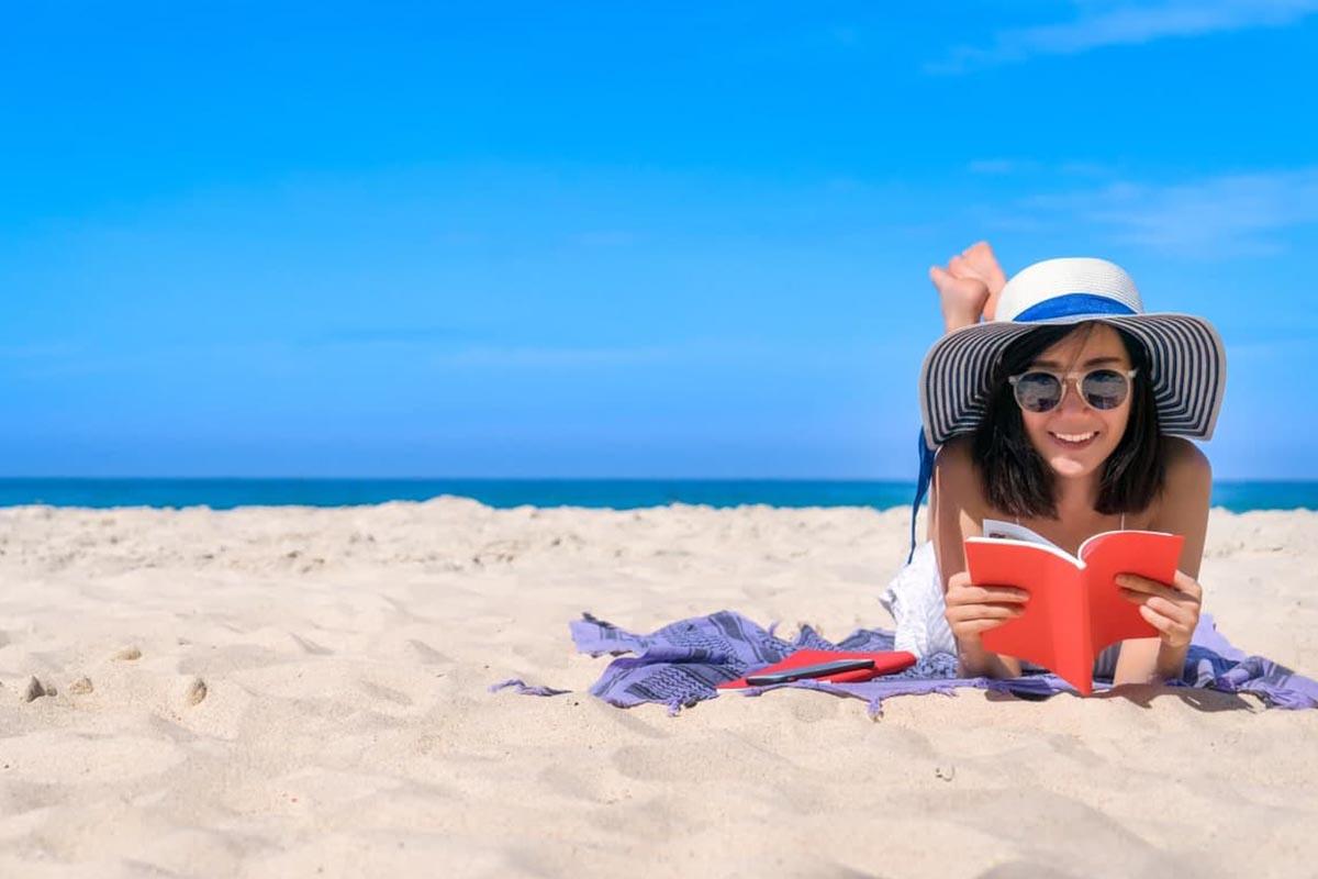 ragazza che legge in spiaggia dei libri con un cappello