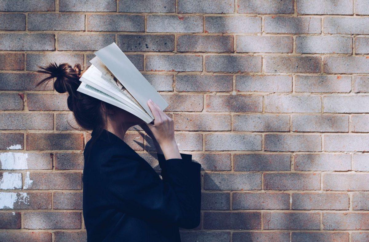 Una ragazza si copre il viso con un libro