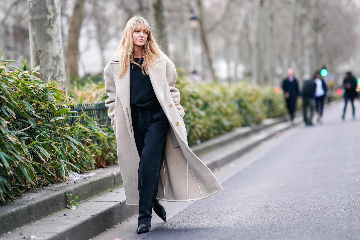 ragazza bionda frangetta cappotto beige jeans maglione nero stivaletti