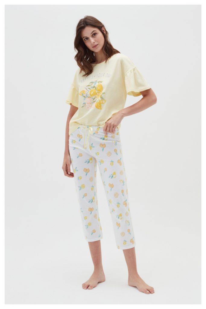 Donna indossa pigiama con fantasia agrumi