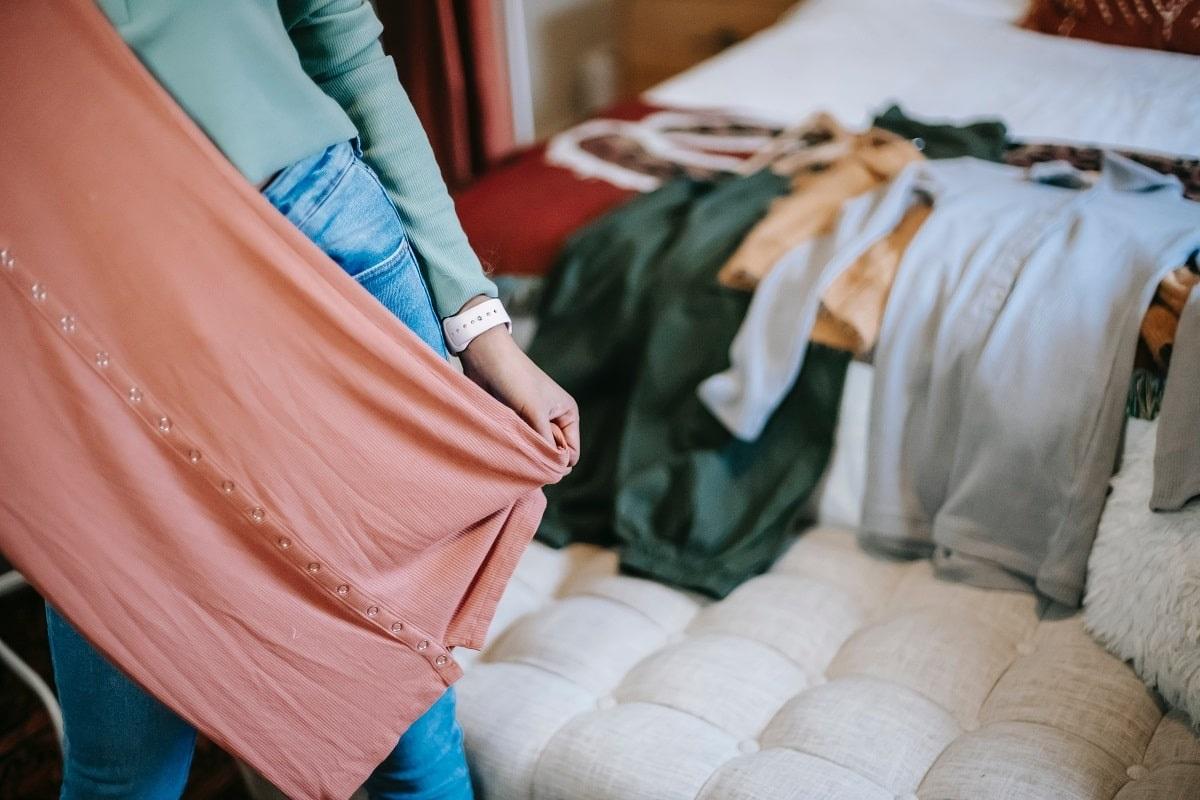 ragazza mostra un abito dal suo guardaroba