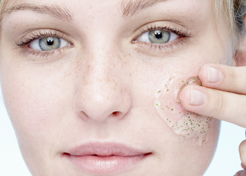 Young woman applying exfoliating gel to face, portrait, close up