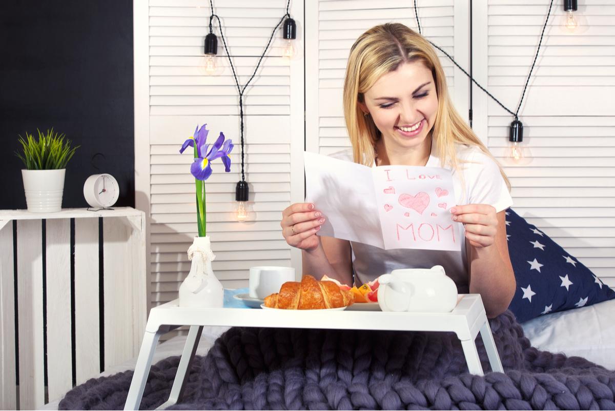 Donna che legge il biglietto per la festa della mamma