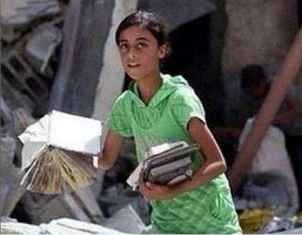 Israele-Palestina: bambina raccoglie libri tra le macerie[FOTO]