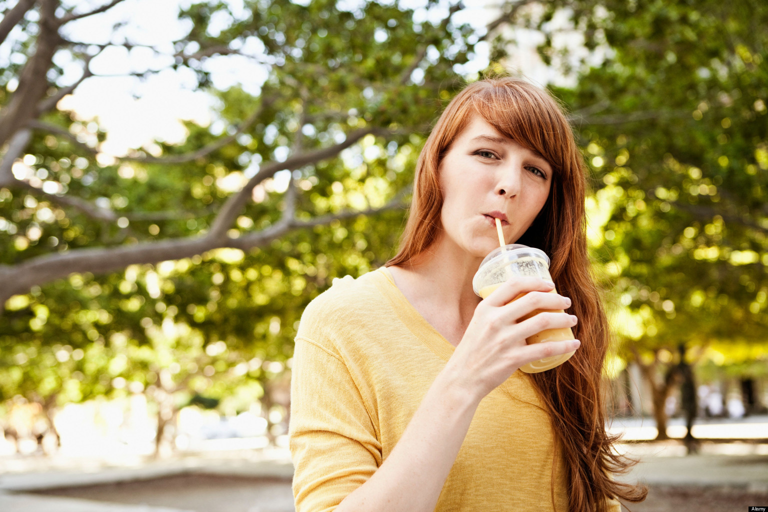 Portrait of young woman drinking milkshake in park