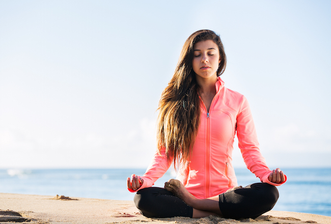 Young woman practicing morning meditation in nature at the beach