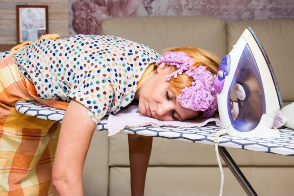 Donna che dorme sull'asse da stiro