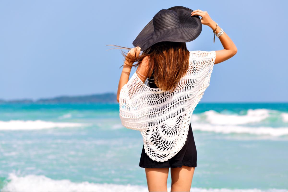 Ragazza al mare di spalle con un cappello di paglia