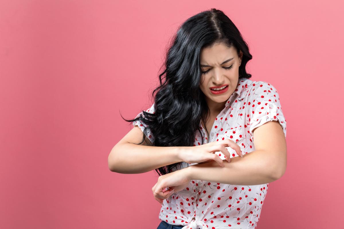 Donna che si gratta il braccio
