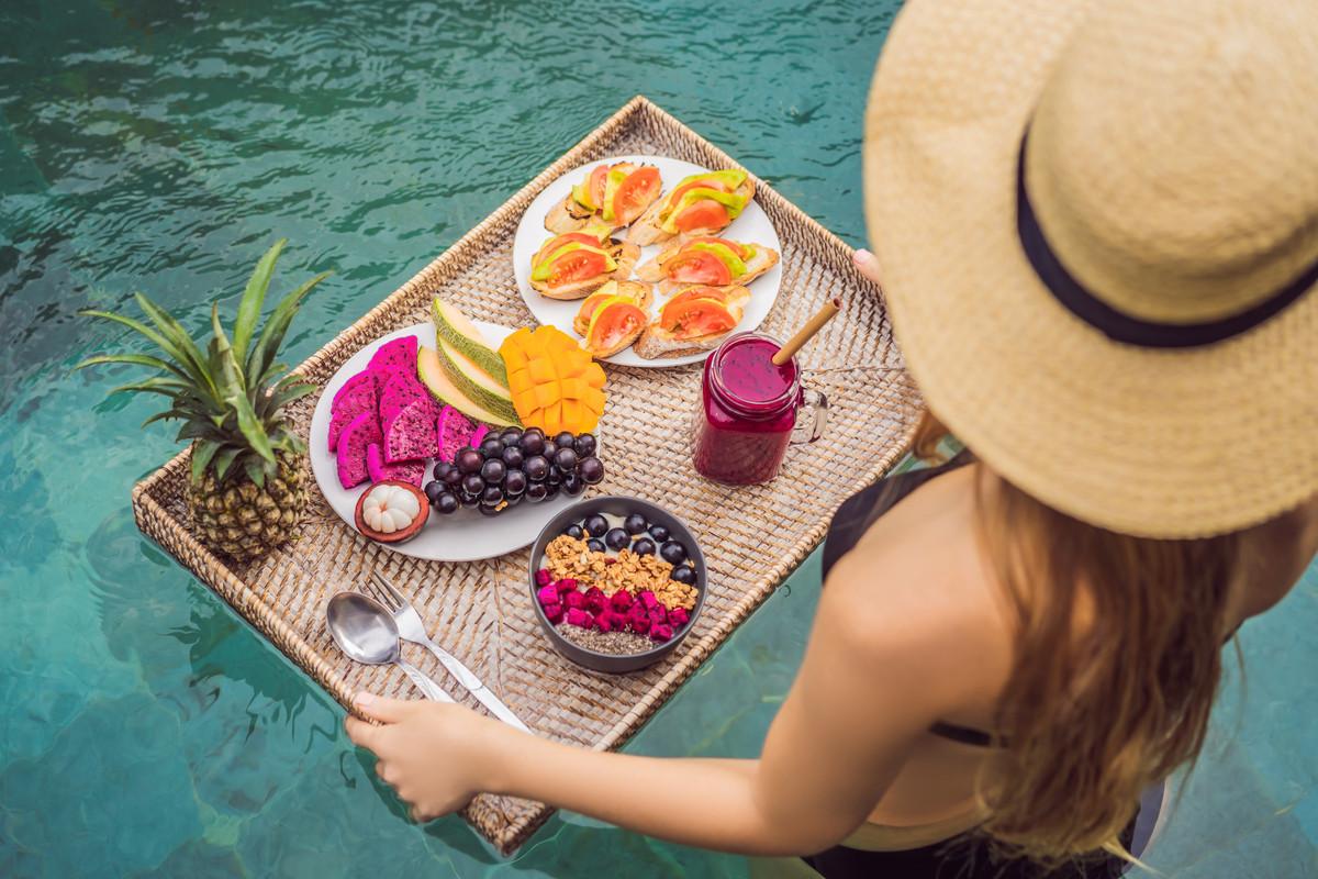 Donna in piscina con un vassoio di frutta