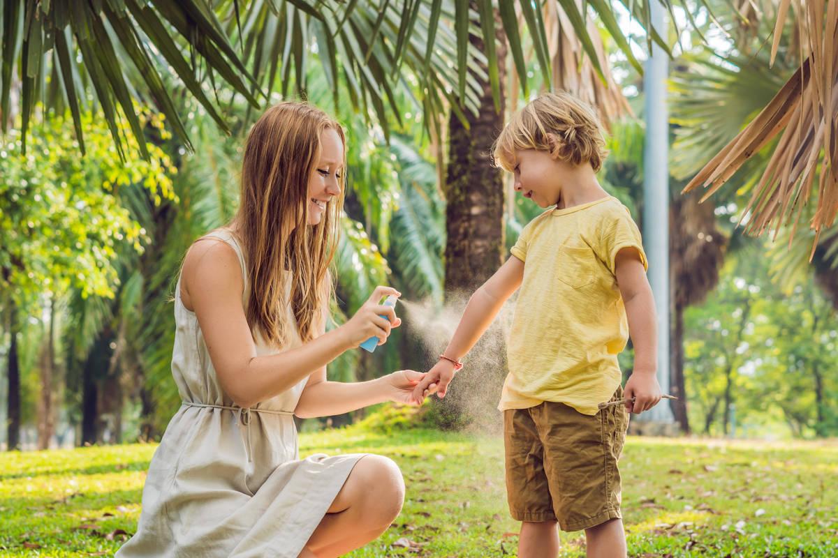 Mamma che mette lo spray anti insetti al figlio
