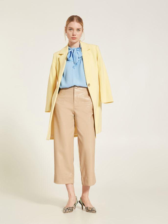 Total look giorno con giacca gialla, pantaloni cropped in ecopelle e camicia con fiocco