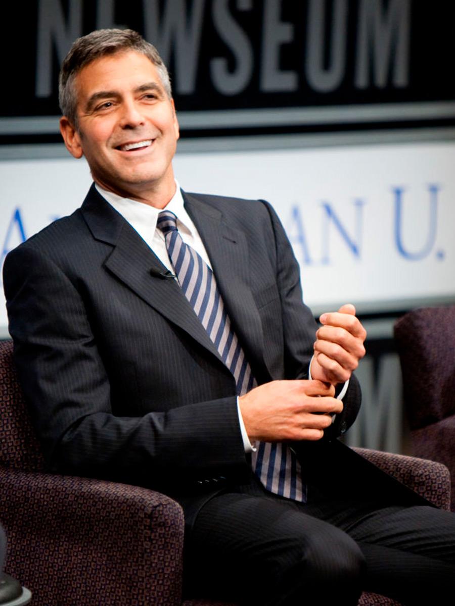 George Clooney seduto in giacca e cravatta