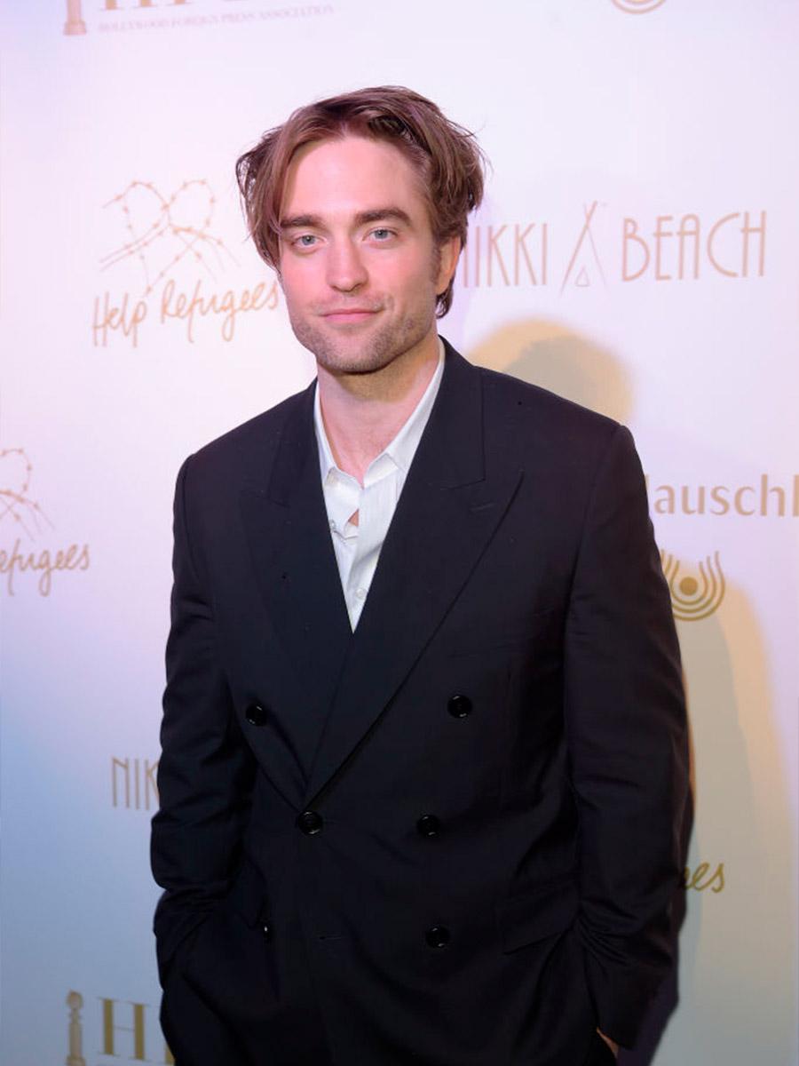 Robert Pattinson sorridente con una giacca scura