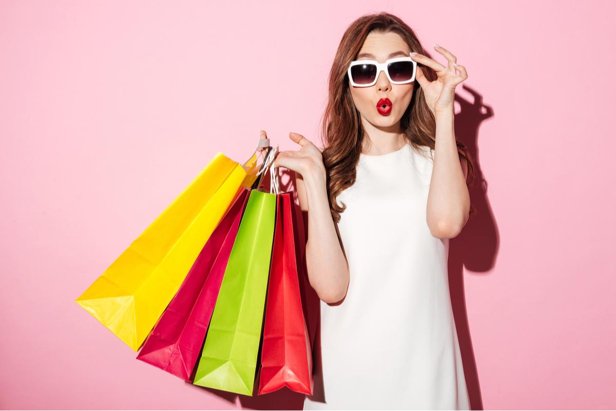 Ragazza con occhiali da sole e buste da shopping