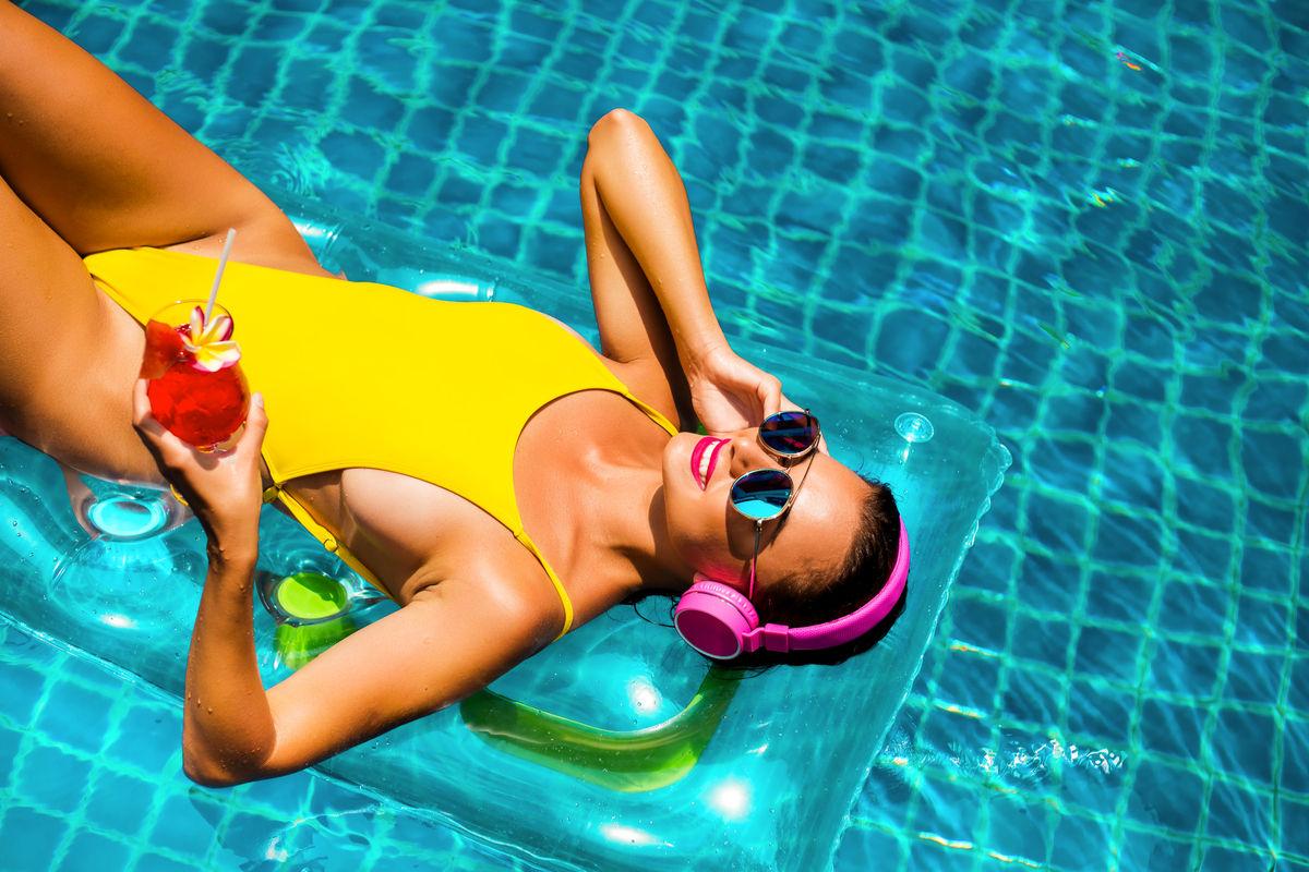Donna in piscina con un costume da bagno giallo
