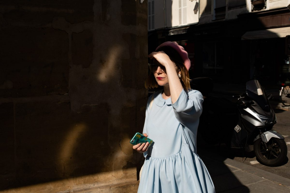 Una ragazza French style con un vestito azzurro, il basco rosa e il rossetto rosso nella penombra