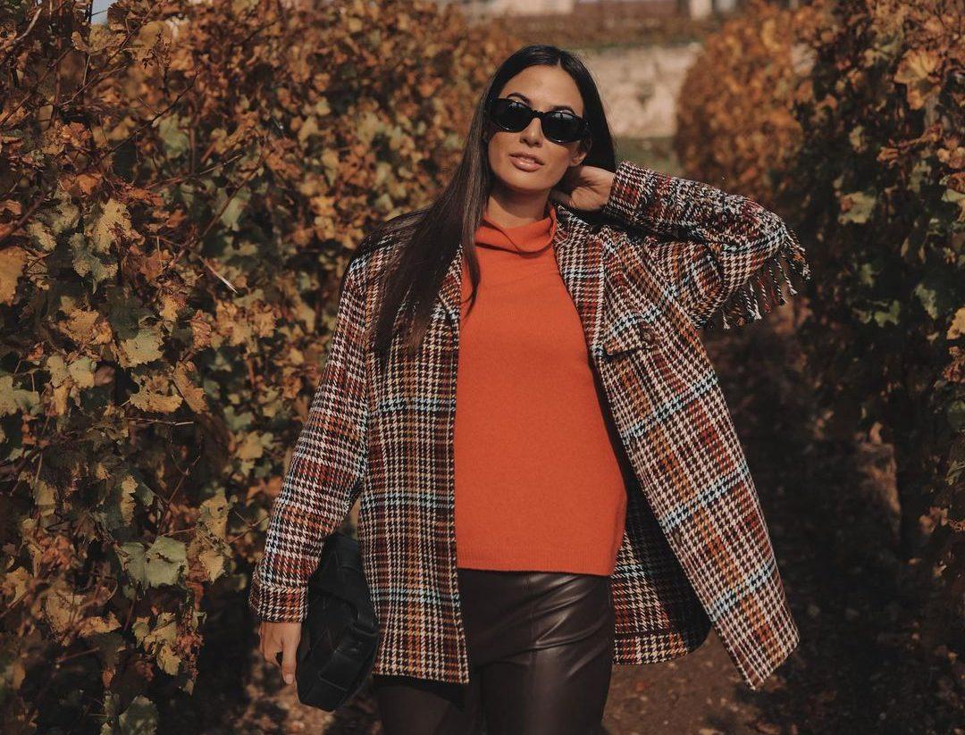 L'influencer Giulia Valentina immersa in paesaggio autunnale con indosso un dolcevita arancione