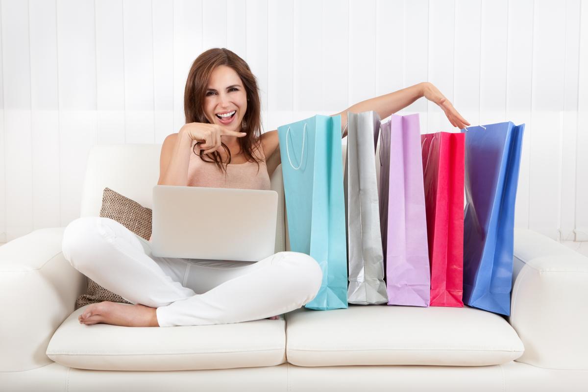Donna sul divano con delle buste da shopping