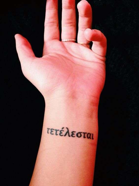 Tatuaggio con frase E' compiuto