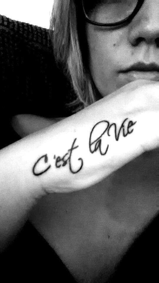Tatuaggio con frase francese C'est la vie sulla mano