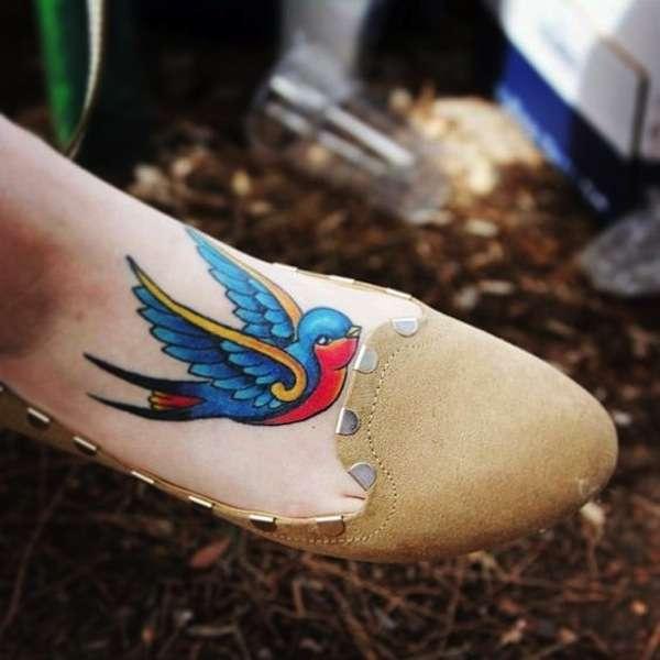 Tatuaggio con rondine colorata sul piede