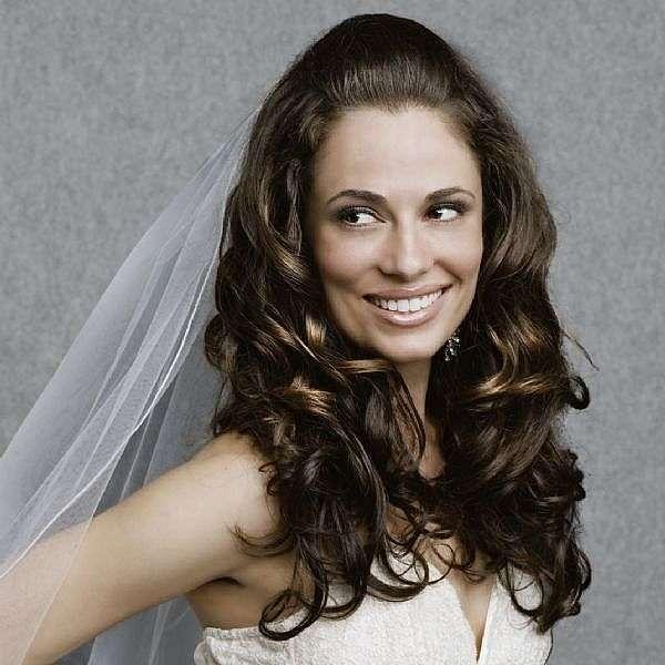 Capelli ricci e lunghi semiraccolti per una sposa
